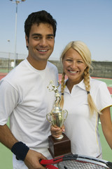Mixed doubles Tennis Players on tennis court holding trophy, portrait