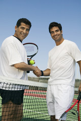 Tennis Players shaking hands over net on court, portrait