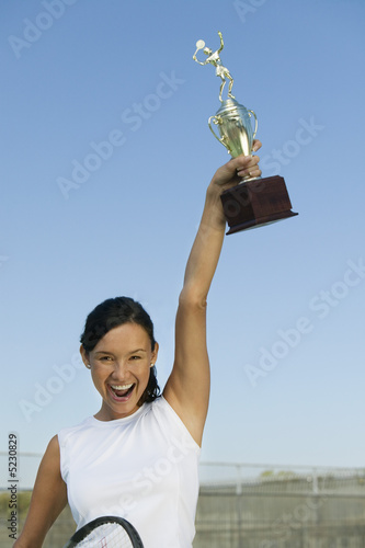 Female tennis player on tennis court holding up trophy, portrait