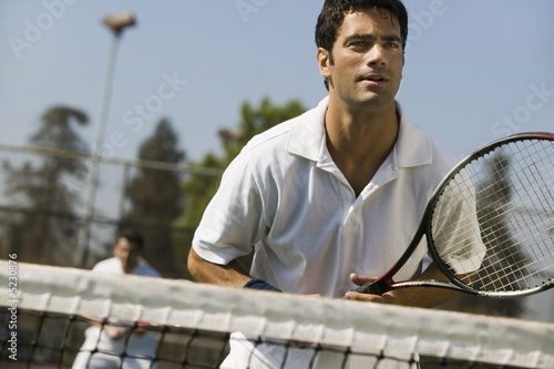 Male doubles tennis players waiting for serve, front view, focus on foreground