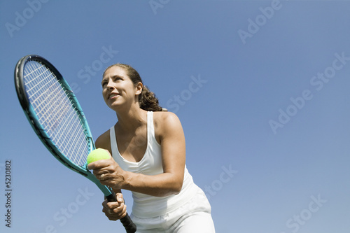Female Tennis Player Preparing to Serve, low angle view