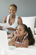 Mother and Daughter on bed Looking at Laptop