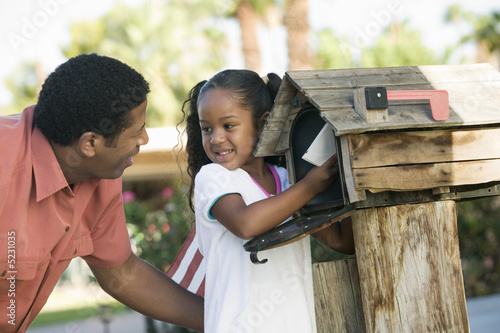 Father and Daughter checking mail at domestic Mailbox