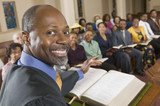 Preacher at altar with Bible preaching to Congregation, portrait, close up