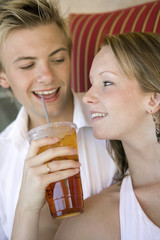 Young couple on sofa, woman giving man iced drink, close up