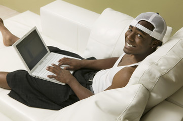 Young man on sofa using laptop, high angle view, portrait