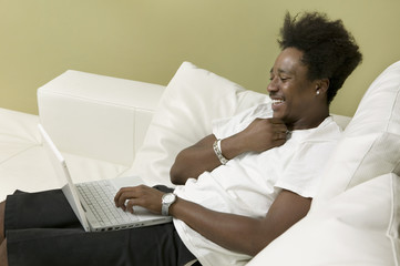 Young man on sofa using laptop, side view