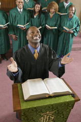 Happy preacher with Bible at church altar looking up, high angle view