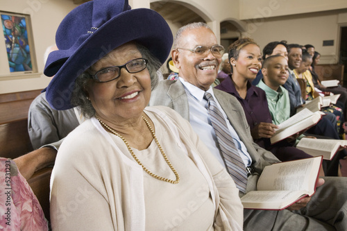 Senior Woman in Sunday Best among congregation at Church, portrait