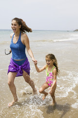 Mother and Daughter Running Through Water on Beach