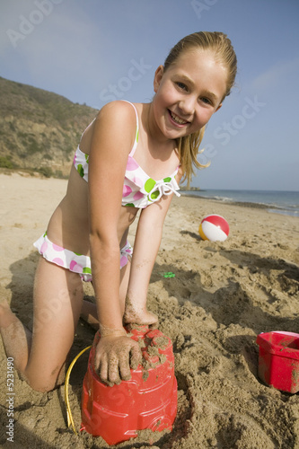 Photo: Young Girl Playing in Sand at Beach