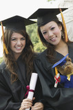 Two graduates holding diploma and teddy bear, portrait