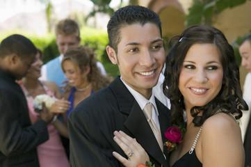 Well-dressed teenage couple embracing outside school dance