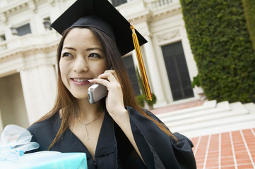Graduate with Gift Using Cell Phone outside