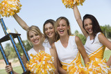 Smiling Cheerleaders holding trophy and pom-poms, portrait