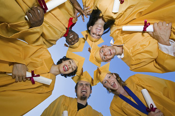 Group of graduates holding diplomas outside, view from below