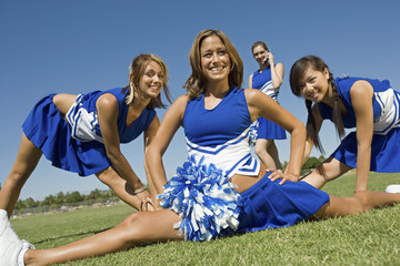 Cheerleaders stretching on lawn, portrait