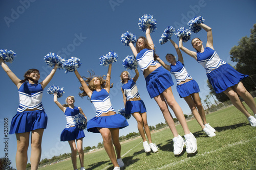 Low angle view of cheerleaders jumping with pom- poms raised against blue sky