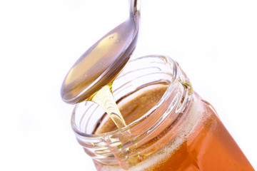 close up of honey jar on white background with clipping path