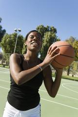 Young woman shooting basketball