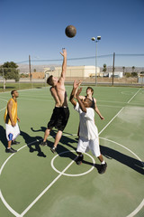 Young men reaching in air for basketball during game