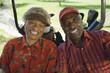 Senior couple sitting in golf cart, smiling, portrait