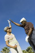 Senior couple giving high-five on golf course, low angle view
