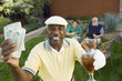 Senior golfers celebrating success, focus on man showing banknotes, portrait