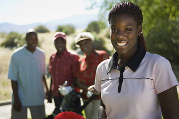 Young woman on golf course, portrait, family in background