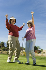 Two women cheering on golf course