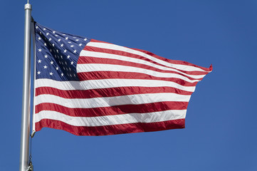 United States flag flapping against clear sky, low angle view