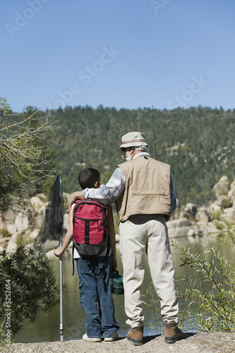 Grandfather and grandson standing by lake, holding fishing rods, back view