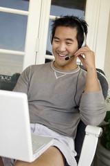 Man wearing headset using laptop on porch