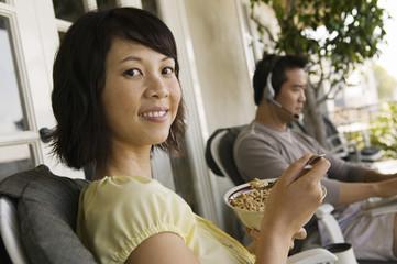 Woman having breakfast on porch, man using laptop in background