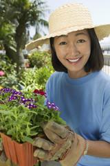 Woman in straw hat gardening, portrait