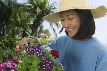 Woman in straw hat clipping flowers in garden
