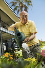 Senior man watering plants in garden, low angle view
