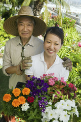 Senior man and daughter gardening, portrait