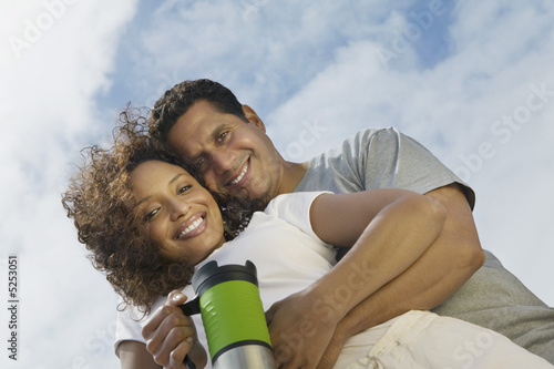 Couple embracing outdoors, portrait, low angle view