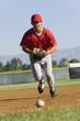 Baseball fielder running towards ball on ground