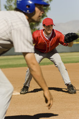Baseball fielder and runner on field, preparing to game
