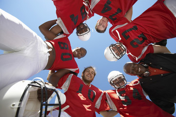 Football Players and Coach in Huddle, view from below, view from below