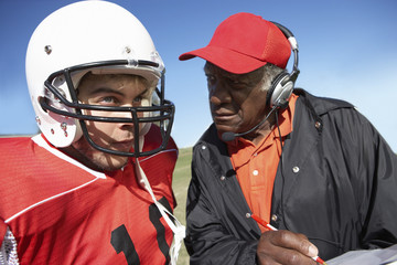 Coach talking to football player, close-up