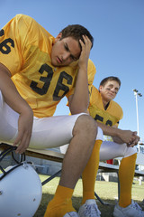 Two football players sitting on bench, low angle view
