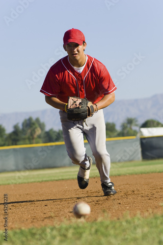 Baseball fielder running towards ball on ground