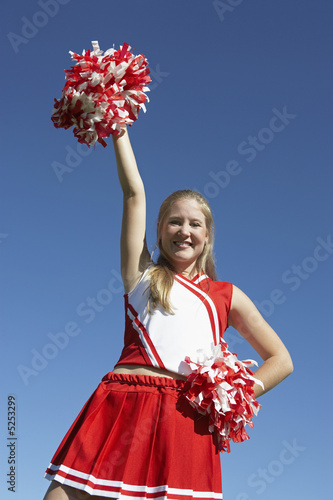 Cheerleader rising pom-pom in air, low angle view, portrait, portrait, low angle view