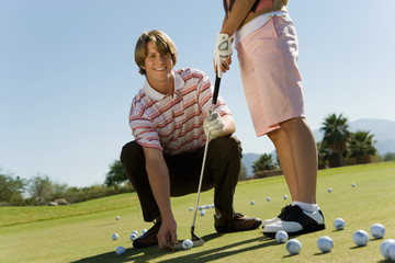 Man teaching teenage girl to putt