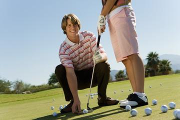 Man teaching teenage girl to putt