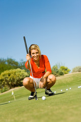Female golfer lining up shot on putting green