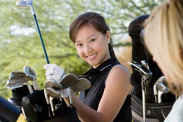 Female golfer choosing club from golf bag, portrait